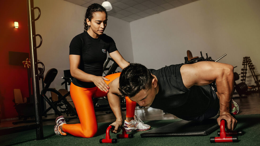 Female personal trainer helping man do push-ups